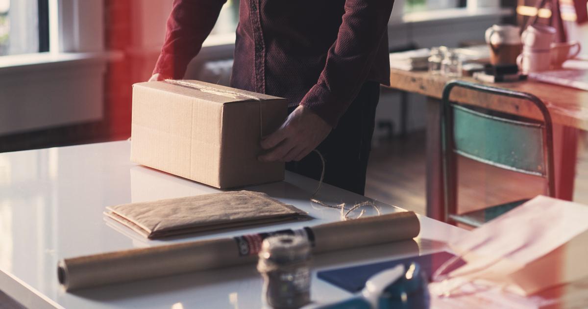 Man pakt een kartonnen doos in.