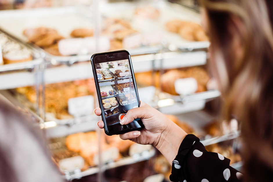 Vrouw neemt een foto van het assortiment met een mobiele telefoon